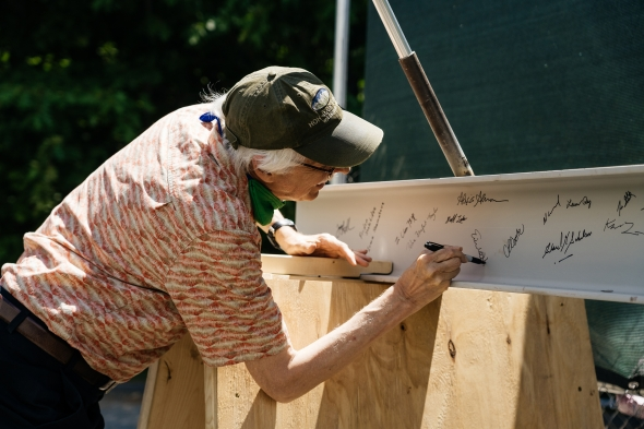 Eric Hansen, an associate professor of engineering at Thayer, signs the beam before it is set into place. (Photo by Eli Burakian '00)